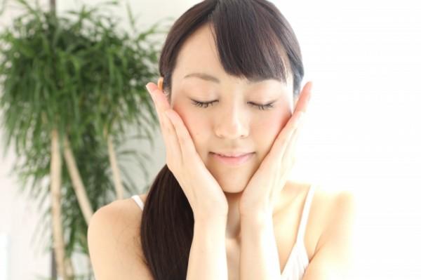 頬に手を当て肌触りを確かめる女性の写真